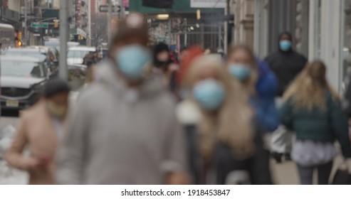 NEW YORK - CIRCA FEBRUARY 2021: Crowd of people walking street wearing masks in SoHo during Covid 19 pandemic