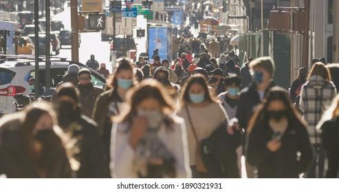 NEW YORK - CIRCA JANUARY 2021: Crowd of people walking street wearing masks