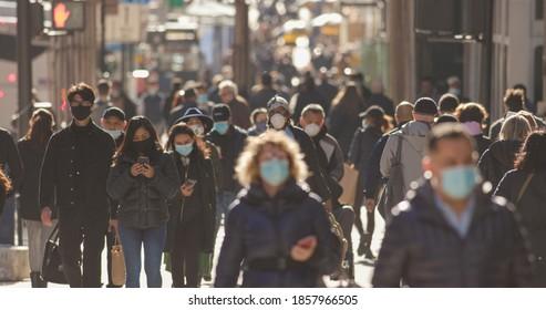 NEW YORK - CIRCA NOVEMBER 2020: Crowd of people walking street wearing masks during covid19 coronavirus pandemic