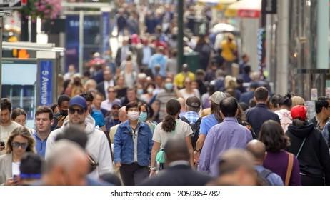 NEW YORK - CIRCA SEPTEMBER 2021: Crowd of people walking street some wearing masks during Covid 19 pandemic