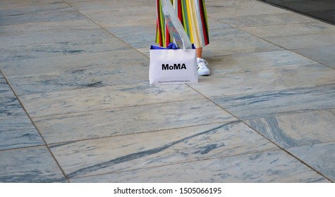 New york city, 05/14/ 2019 /imagen / Woman wearing colorful skirt, on the floor of the museum Moma, posing with shop bag MoMa