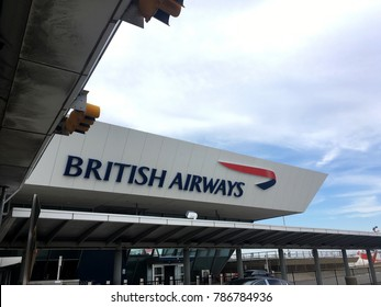 New York City - 10 August 2017: Entrance to the British Airways airline terminal at JFK airport in New York City. British Airways sign at the airport against clouds and blue skies.