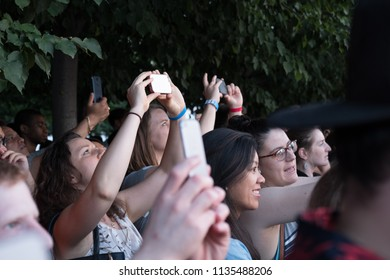 New York City - 12 July 2018: Group of people taking a picture of Manhattanhenge through a crowd of people on Roosevelt Island as the suns sets perfectly between New York skyscrapers.