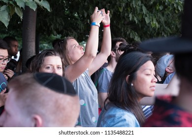 New York City - 12 July 2018: Woman stretches her arms high to go above the crowd to take photographs of Manhattanhenge from Roosevelt island. Crowd of people taking photos during Manhattanhenge.