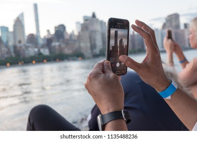 New York City - 12 July 2018: People taking photographs from Roosevelt Island in the East River during Manhattanhenge as the sun set between the skyscrapers in Manhattan. Man takes photo with phone.