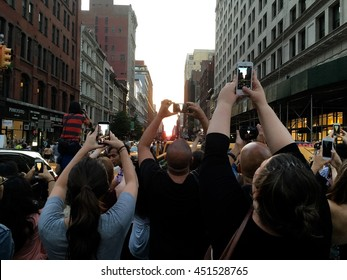 NEW YORK CITY - 12 JULY 2016: A crowd of people stand in the intersection of Broadway and 23rd street to take photos of Manhattanhenge