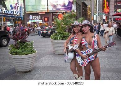 new york city, 12 september 2015: two naked cowgirls in bikini play guitar on times square manhattan new york city