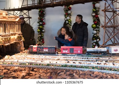 New York City - 13 January 2018: Little Asian boy points to show something to his grandmother while a model train goes by at the New York Botanical Garden Holiday Train Show in the Bronx.