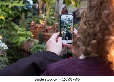 New York City - 13 January 2018: A caucasian woman takes a photo with her mobile phone in the atrium at the New York Botanical Garden holiday train show.