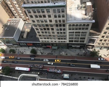 New York City - 15 June 2017: Looking down on 34th Street from the Empire State Building at shops and open roofed double decker red tour bus. People traveling down 34th street in Midtown Manhattan.