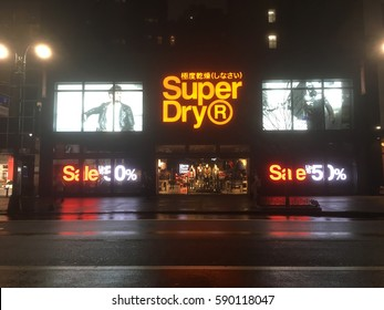 New York City - 20 January 2017: SuperDry, Japanese clothing retailer, in Midtown New York at night after the rain. Car taillights of passing vehicle SuperDry exterior from the street. 50% sale signs.