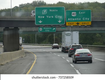 NEW YORK CITY, USA—SEPTEMBER 2017:  Directional signs on an overpass bridge with arrows pointing to the directions of new York City and Atlantic City exit.