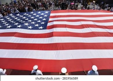 NEW YORK CITY - 25 MAY 2015: Mayor Bill de Blasio & Gen John Kelly presided over Memorial Day observances on Pier 86 by the USS Intrepid. Unfurling massive US flag on pier 86