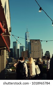 New York City - 26 June 2017: People enjoying a drink on rooftop bar Bar Hugo in Lower Manhattan. String of lights and views of Manhattan skyline and Freedom Tower in the background.