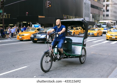 New York City, 26 May 2016: man on taxi bike waits for clients in fifth Avanue new york