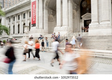 New York City - 29 July 2017: Motion blur from slow shutter speed walking up the steps to the front entrance of the main branch of the New York Public Library on Fifth Avenue in New York City.