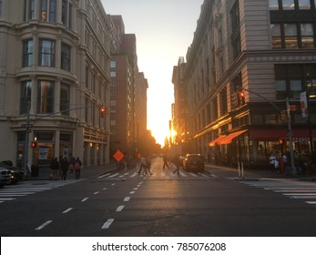 New York City - 31 May 2017: Manhattanhenge in New York. Sun setting between buildings on 23rd Street in Flat Iron District. People crossing street in zebra crossing during Manhattan henge.