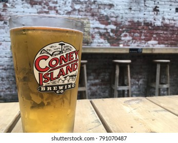 New York City - 8 August 2017: Glass of Coney Island pilsner on a wood table in the backyard of a pub in New York. Three wooden stools in background. Coney Island Brewing Company beer.
