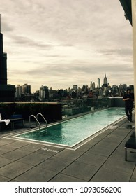 New York City - 8 June 2017: Hotel Indigo rooftop swimming pool with view of the Empire State Building and midtown Manhattan from the rooftop.