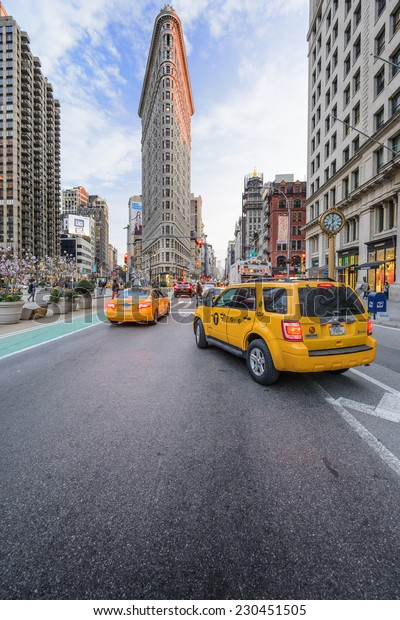 NEW YORK CITY - APRIL 15, 2014: Taxis stop under the Flatiron Building. Finished in 1902, the landmark skyscraper was designated a City Landmark in 1966 and a National Historic Landmark in 1989.