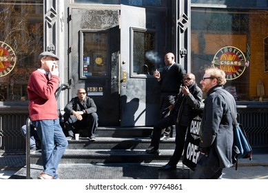 NEW YORK CITY - APRIL 2: Smokers puffing on cigars in front of a cigar shop in Soho, New York City on April 2, 2012. The city's anti-smoking laws prohibit smoking outdoors in parks and public squares.