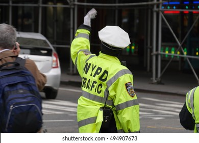New York City - April 2016: NYPD police officer direct traffic during the busy morning commute in Midtown Manhattan. Direction signal to ensure safety for driver and pedestrians in crosswalk