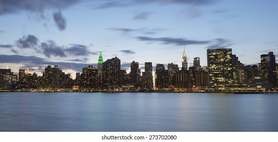 NEW YORK CITY - APRIL 22: New York City Manhattan skyline with Empire State Building, Chrysler Building and United Nations building at night over East River on April 22, 2015 in New York City.