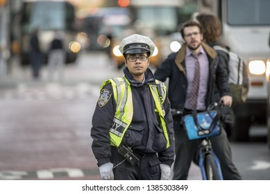 NEW YORK CITY - APRIL 30, 2019: Young NYPD Police officer in NYC  regulating traffic on city streets in the midst of intense traffic during a classic working day of the week.