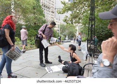 NEW YORK CITY - AUGUST 1 2016: ShutdowncityhallNYC continued its occupation of city hall park into the afternoon & evening with a rally & speeches from activists. Selling copies of Wokers' Vanguard