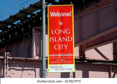 New York City - August 10, 2008:  Welcome to Long Island City BID banner hangs from a lamp post underneath subway elevated tracks near Queens Plaza