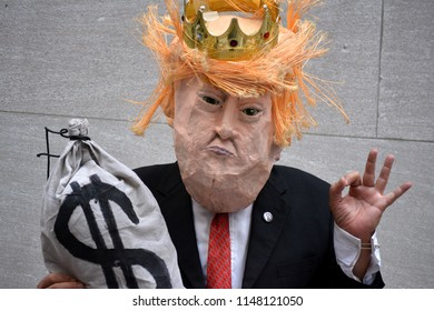 New York City - August 2, 2018: Protester in a Donald Trump mask at a demonstration against ICE on Wall Street in Lower Manhattan.