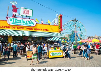 NEW YORK CITY - AUGUST 20, 2017: Visitors crowd the iconic wooden Coney Island boardwalk outside the famous Nathan's hot dog stand on a hot summer day in Brooklyn.
