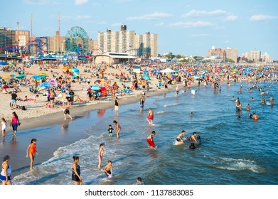 NEW YORK CITY - AUGUST 20, 2017: View of people enjoying a summer's day on crowded Coney Island beach and boardwalk.