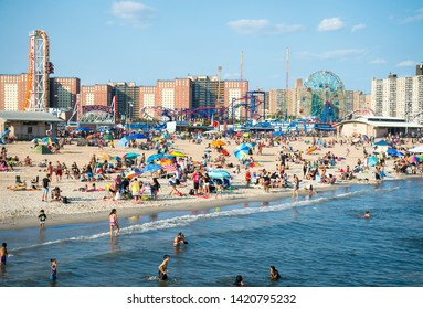 NEW YORK CITY - AUGUST 20, 2017: Crowds of people flock to the Coney Island beach and boardwalk on a hot summer weekend.
