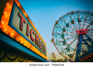 NEW YORK CITY - AUGUST 20, 2017: The bright lights of the amusement park at Coney Island in Brooklyn glow in front of a summer dusk sky.
