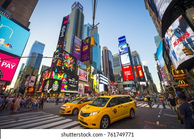 NEW YORK CITY - AUGUST 23, 2017: Bright neon signage flashes over crowds and taxi traffic zooming through Times Square.