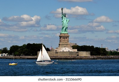 New York City - August 27, 2015:  Sailboat passing the Statue of Liberty by French sculptor Frederic-Auguste Bartholdi on Bedloe's Island at the entry to NY harbor
