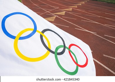 NEW YORK CITY - AUGUST 30, 2015: Olympic flag waves across the lanes of a traditional red tartan running track.
