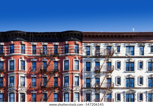 New York City block of old historic apartment buildings in the East Village of Manhattan, NYC with a clear blue sky background