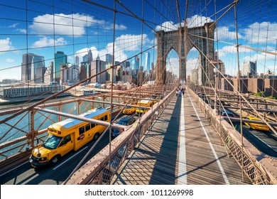 New York City Brooklyn Bridge at sunny day with Yellow taxis / Cabs at the road. Beautiful Clouds behind Manhattan buildings