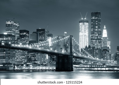 New York City Brooklyn Bridge black and white with downtown skyline over East River.