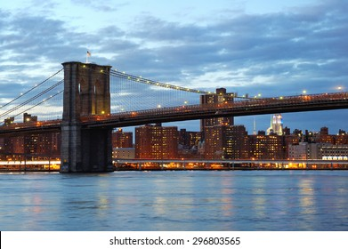 New York City Brooklyn Bridge with downtown skyline over East River at dusk