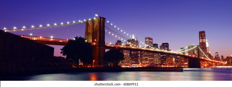 New York City Brooklyn Bridge and Manhattan skyline panorama view with skyscrapers over Hudson River illuminated with lights at dusk after sunset.