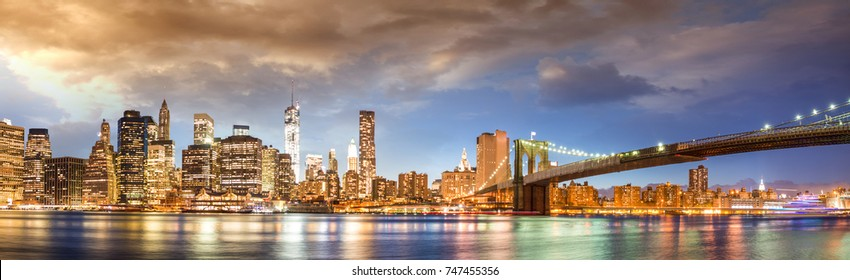 New York City Brooklyn Bridge and Manhattan skyline with skyscrapers over Hudson River illuminated with lights at dusk after sunset