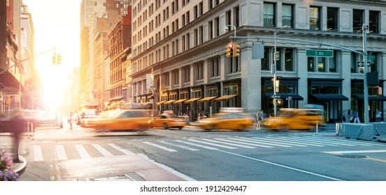 New York City - Busy intersection with yellow taxis speeding through the crowded intersection of 5th Avenue and 23rd Street with the light of sunset shining in the background