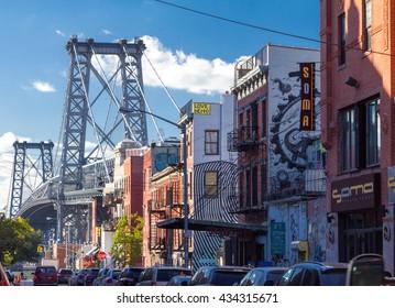 NEW YORK CITY - CIRCA 2015: Cars line the street in a neighborhood near the Williamsburg Bridge in Brooklyn, New York City in the Fall 2015. The bridge connects Manhattan with Brooklyn.