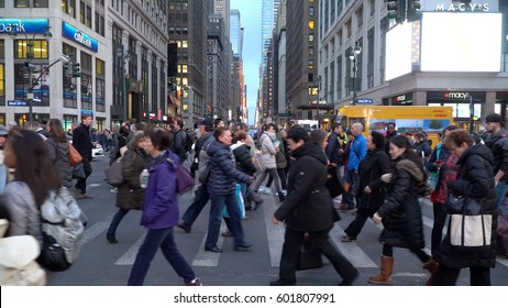 New York City - Circa 2017: Busy people walking in pedestrian crosswalk across 7th avenue midtown Manhattan during evening commute. Street view towards times square with neon lights shining on block