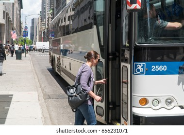 New York City, Circa 2017: Woman enters MTA Bus on Manhattan 5th avenue during day time commute. People use public transportation to navigate through heavy traffic streets