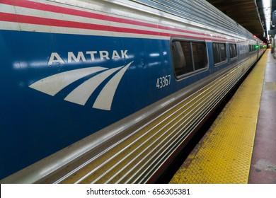 New York City, Circa 2017: Amtrak train at Penn Station railroad terminal platform Manhattan. Red White and Blue logo. Long distance business rail commute travel