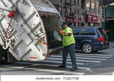 New York City, Circa 2017: DSNY Sanitation department workers empty trash can into garbage truck to keep street clean